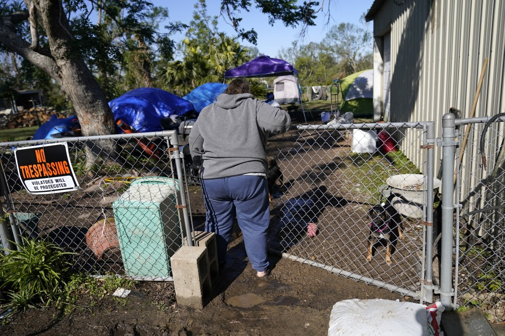 Sherry Bourque enters the back yard of her fathers heavily damaged home, where she is living in a tent, in the aftermath of both Hurricane Laura and H...