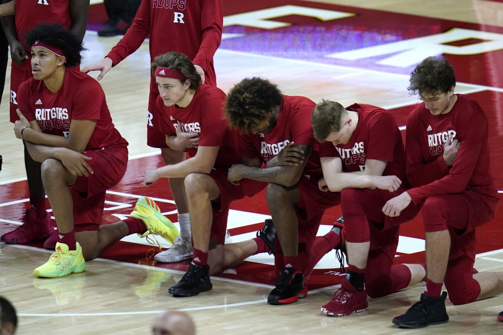 FILE - In this Dec. 14, 2020, file photo, members of the Rutgers men's basketball team take a knee during the playing of the national anthem prior to ...