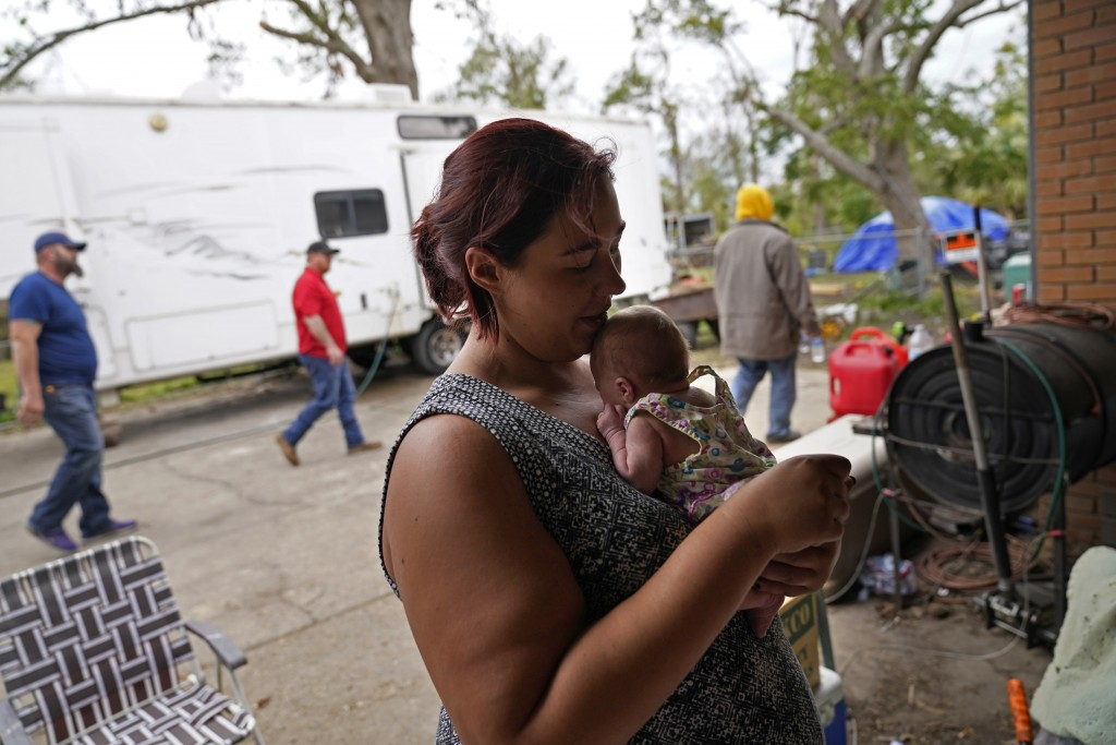Hannah Bourque holds one of her two-week old twins outside the camper she is living in with her grandfather, while her mother lives in a tent in the b...