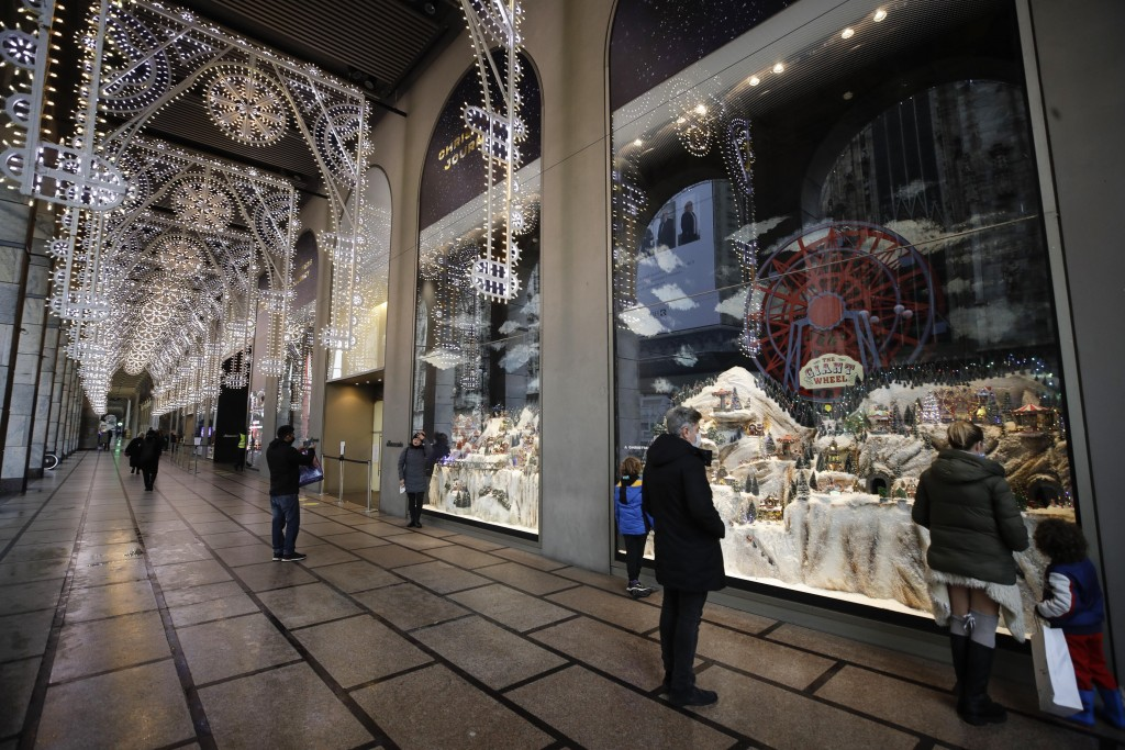 People look at a shop window adorned with Christmas decorations in Milan, Italy, Thursday, Dec. 24, 2020. Italy went into a modified nationwide lockdo...
