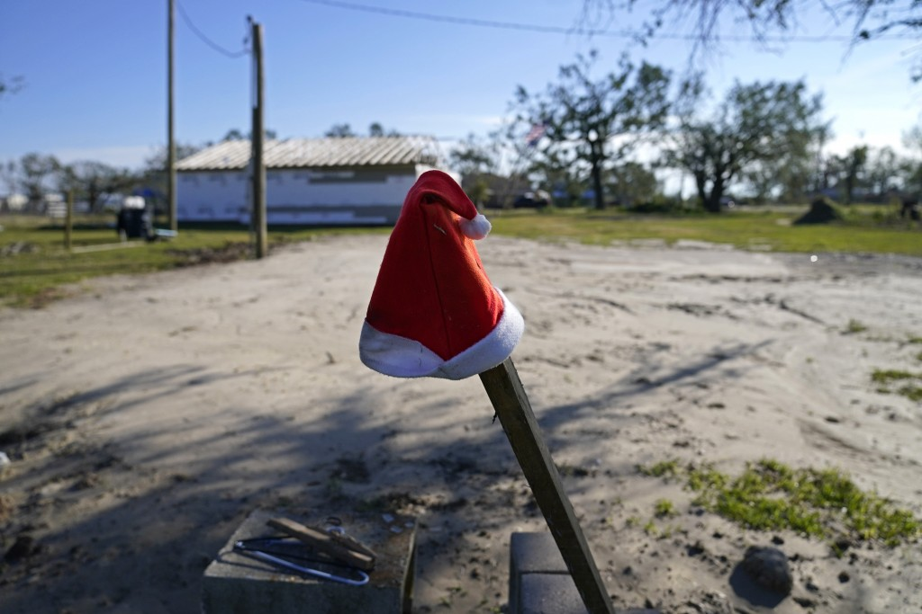 A Santa hat sits on a pole on a lot where Dewana Young's mother's home once stood before Hurricane Laura and Hurricane Delta, in Grand Lake, La., Frid...