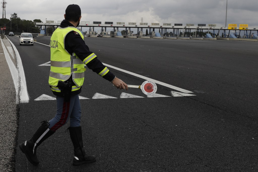 An Italian Police officer stops a car leaving the highway to enter Rome, Thursday, Dec. 24, 2020. Italians are easing into a holiday season full of re...