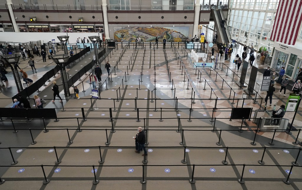 FILE - Travelers head through the south security checkpoint check in the terminal of Denver International Airport, Thursday, Dec. 10, 2020, in Denver....