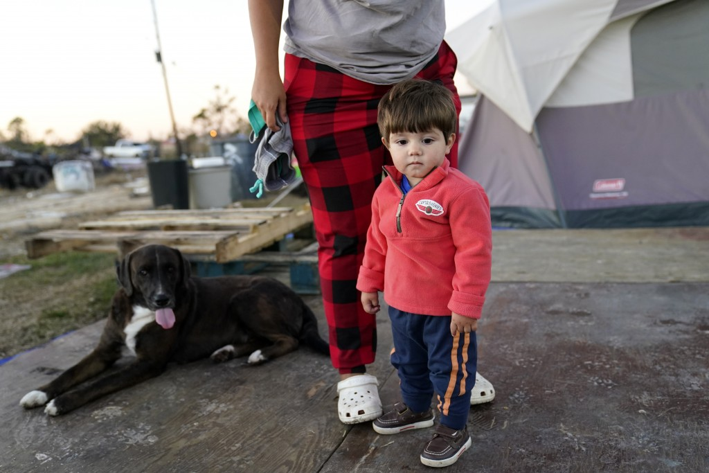 Katelyn Smith stands with her one year old son Ricky Trahan, III, as she prepares to change his clothes, as their family lives in a camper and tents w...