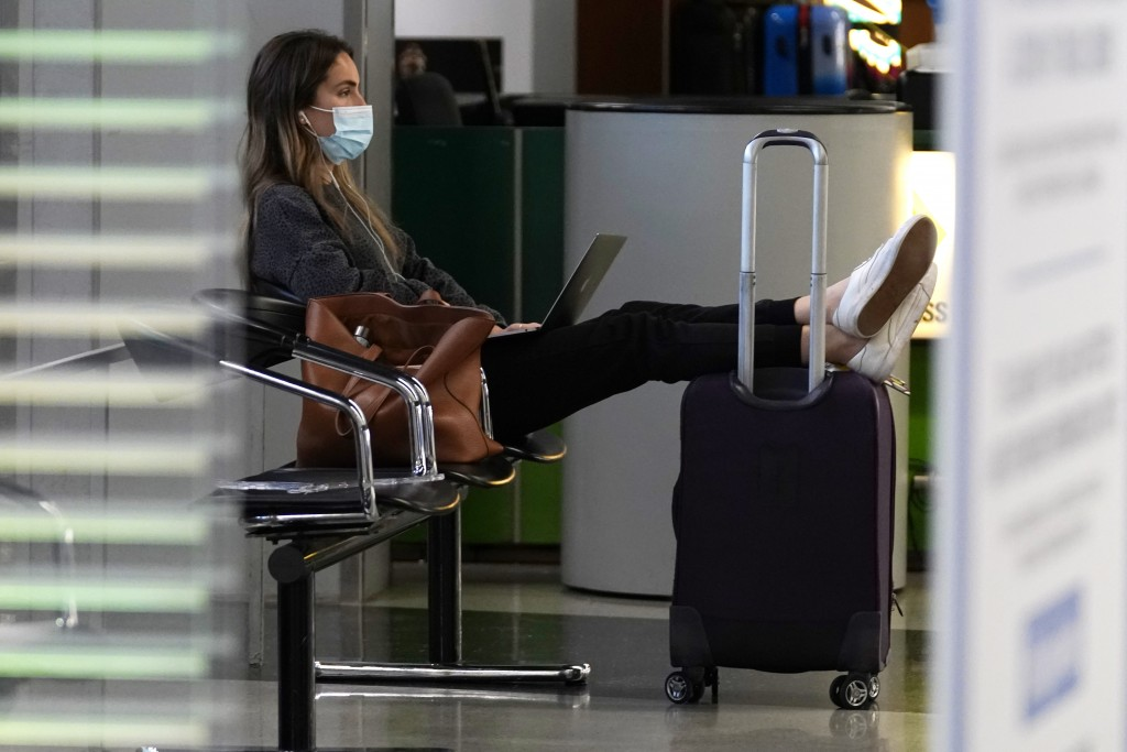 FILE - A traveler wears a mask as she waits for her flight in Terminal 3 at O'Hare International Airport in Chicago, Sunday, Nov. 29, 2020.  The coron...