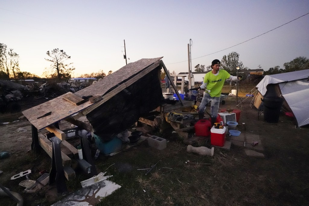 Ricky Trahan runs an extension cord to set up a light, where he now lives in a tent with his wife, in the aftermath of Hurricane Laura and Hurricane D...