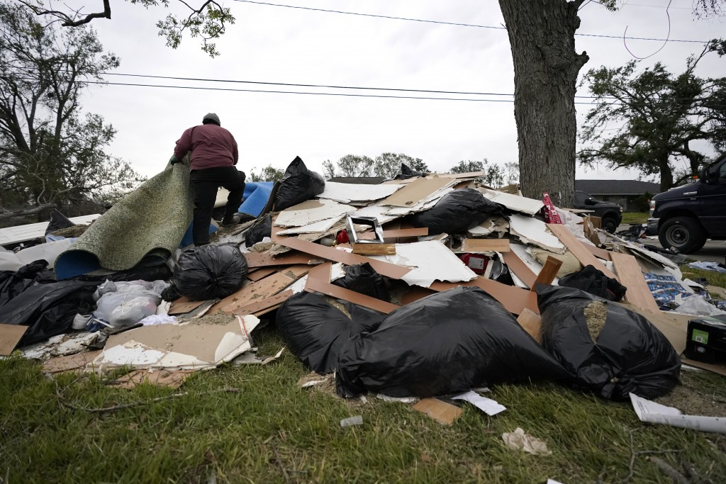 Khalif Kinnie throws debris on a pile from a heavily damaged home he was hired to gut, in the aftermath of Hurricane Laura and Hurricane Delta, in Lak...