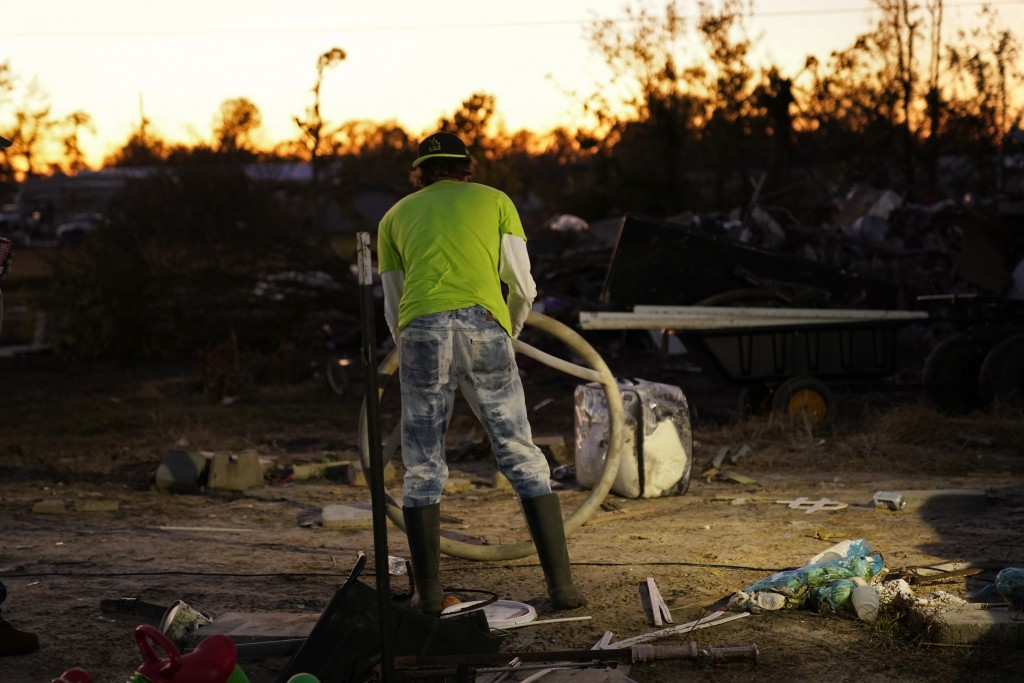 Ricky Trahan sorts debris from his destroyed home, where he now lives in a tent with his wife, in the aftermath of Hurricane Laura and Hurricane Delta...