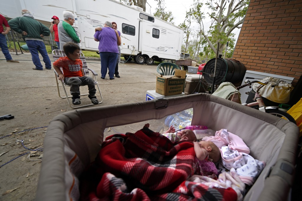 Two-week old twins Lilly and Zoey lay in a bassinet as Hannah Bourque hugs church volunteers who brought Christmas presents to her son Conner, seated,...