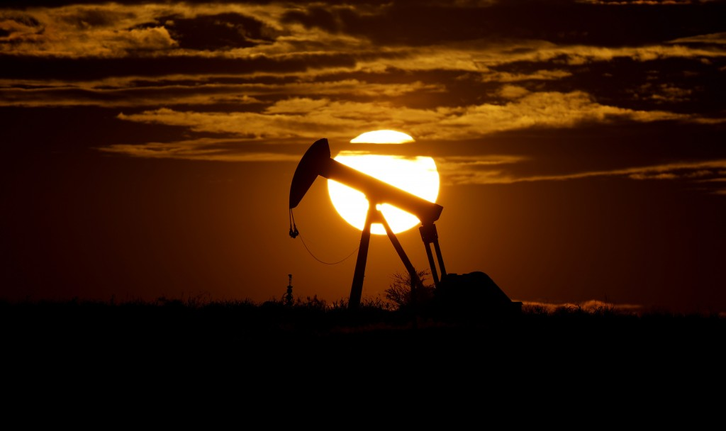 FILE - In this Wednesday, April 8, 2020, file photo, the sun sets behind an idle pump jack near Karnes City, Texas. In 2020, the coronavirus pandemic ...