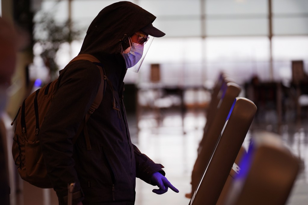 FILE - In this Nov. 24, 2020 file photo, an air traveler checks in wearing a protective mask, face shield and protective gloves, for his flight on Sou...