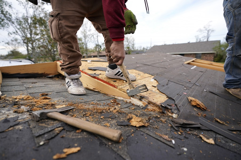 Roofers work on the heavily damaged and gutted home of Christi and Brandy Monticello, in the aftermath of Hurricane Laura and Hurricane Delta, in Lake...