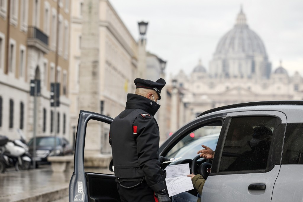 Italian Carabinieri officers check vehicles in front of St. Peter's Basilica at the Vatican, Thursday, Dec. 24, 2020. Italians are easing into a holid...