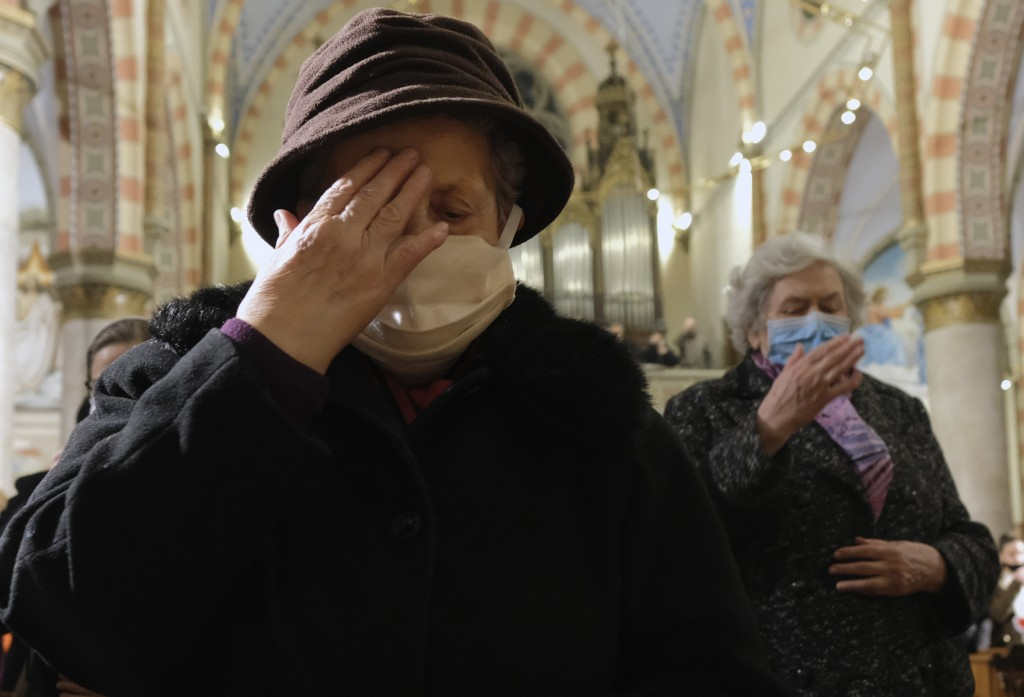 People wearing masks for protection against COVID-19 attend a Christmas Eve Mass at the Sacred Heart Cathedral in the capital Sarajevo, Bosnia, Thursd...
