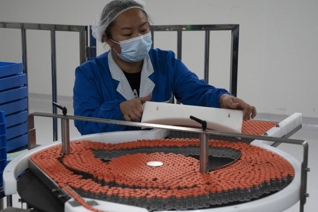 A worker loads vials to be used in the production line for a vaccine for COVID-19 at Chinese company Sinovac at its factory in Beijing on Thursday, Se...