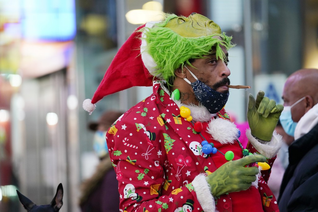 A man dressed in Christmas garb smokes a hand-rolled cigarette, Thursday, Dec. 24, 2020, in Times Square on Christmas Eve in New York. (AP Photo/Kathy...