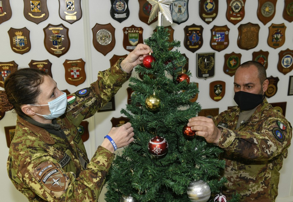 In this photo provided by NATO-led peacekeeping mission in Kosovo (KFOR), Italian soldiers decorate Christmas tree on the Christmas Eve in the KFOR mi...
