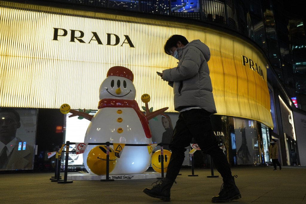 A man wearing a mask to protect from the coronavirus past by a Christmas decoration in Beijing on Friday, Dec. 25, 2020. Official churches in the Chin...