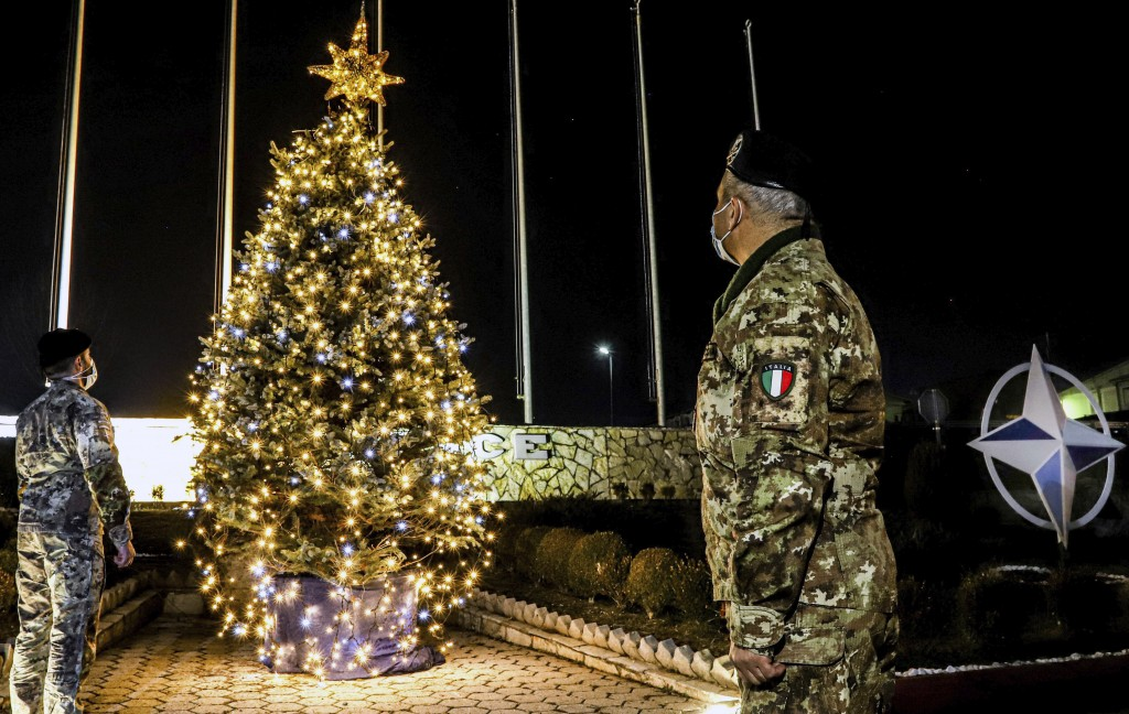 In this photo provided by NATO-led peacekeeping mission in Kosovo (KFOR), Italian soldiers watch Christmas tree on the Christmas Eve in the KFOR milit...