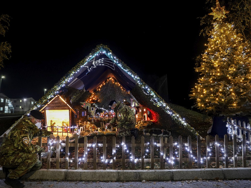 In this photo provided by NATO-led peacekeeping mission in Kosovo (KFOR), Italian soldiers decorate lights on the Christmas Eve in the KFOR military h...