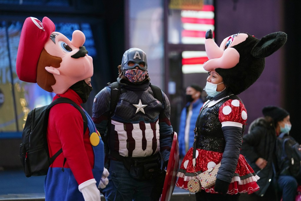People in costumes take a break from posing for photographs with passersby, Thursday, Dec. 24, 2020, on Christmas Eve in New York. (AP Photo/Kathy Wil...