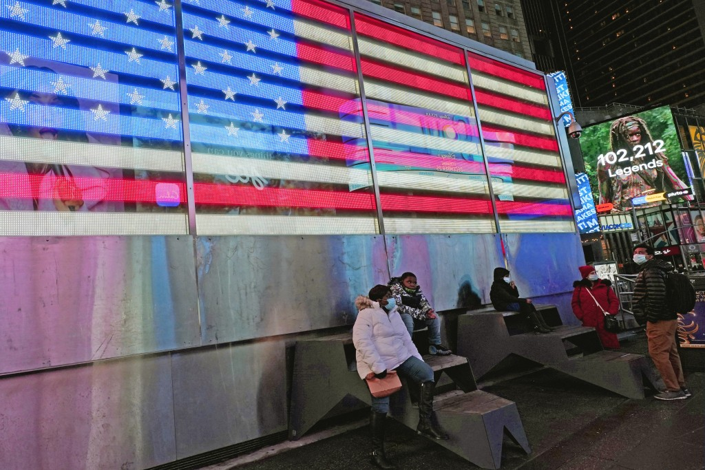 People rest on steps in front of an illuminated American flag in Times Square, Thursday, Dec. 24, 2020, on Christmas Eve in New York. (AP Photo/Kathy ...
