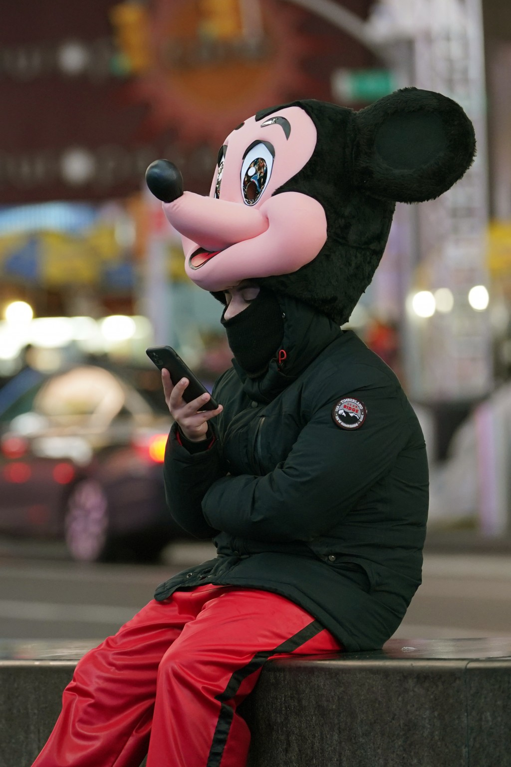 A person dressed as Mickey Mouse takes a break from posing for photographs with people in Times Square, Thursday, Dec. 24, 2020, on Christmas Eve in N...
