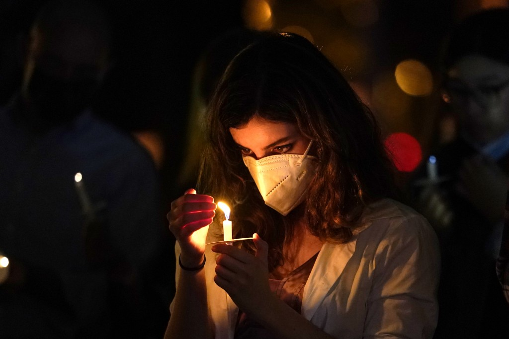 A woman wears a protective face mask while holding a candle during an outdoor Christmas Eve Service of Lights at the Granada Presbyterian Church, Thur...
