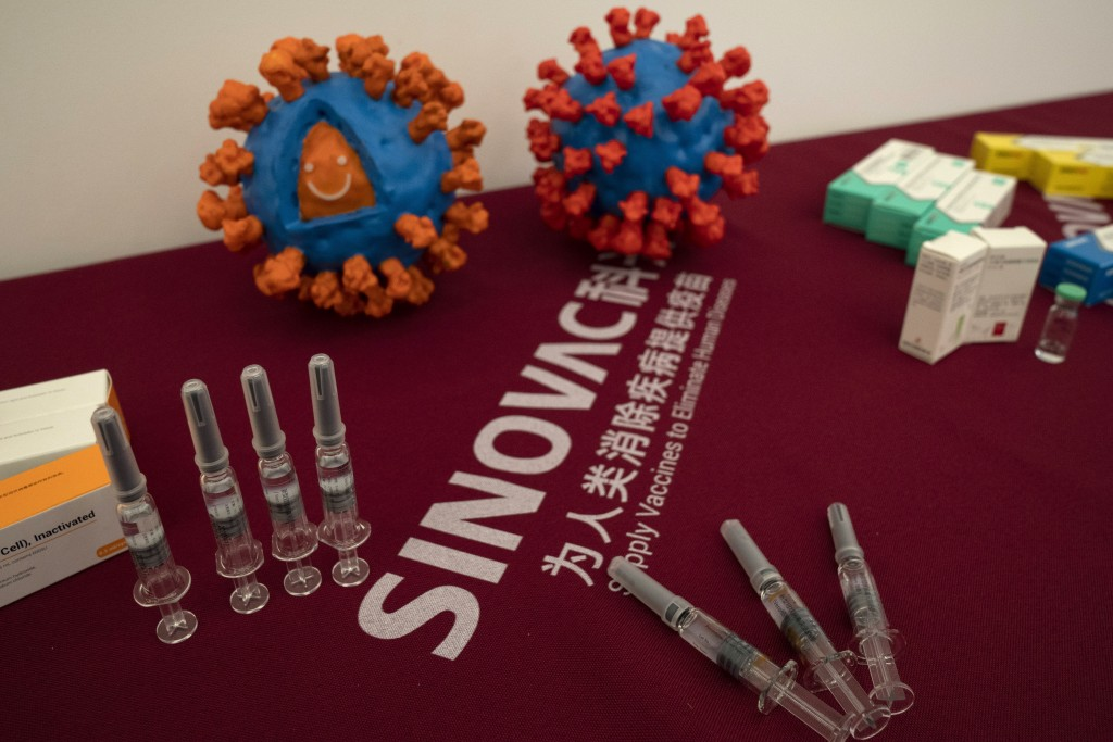 Syringes of a vaccine for COVID-19 and models depicting the coronavirus are displayed at the Sinovac factory in Beijing on Sept. 24, 2020.