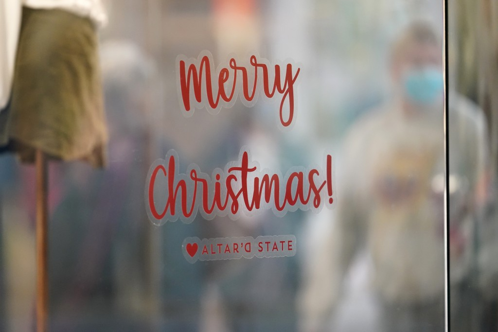 """A sign bids visitors """"Merry Christmas!"""" in the window of a clothing store as last-minute shoppers wear face masks as they search for Christmas Eve dea..."""