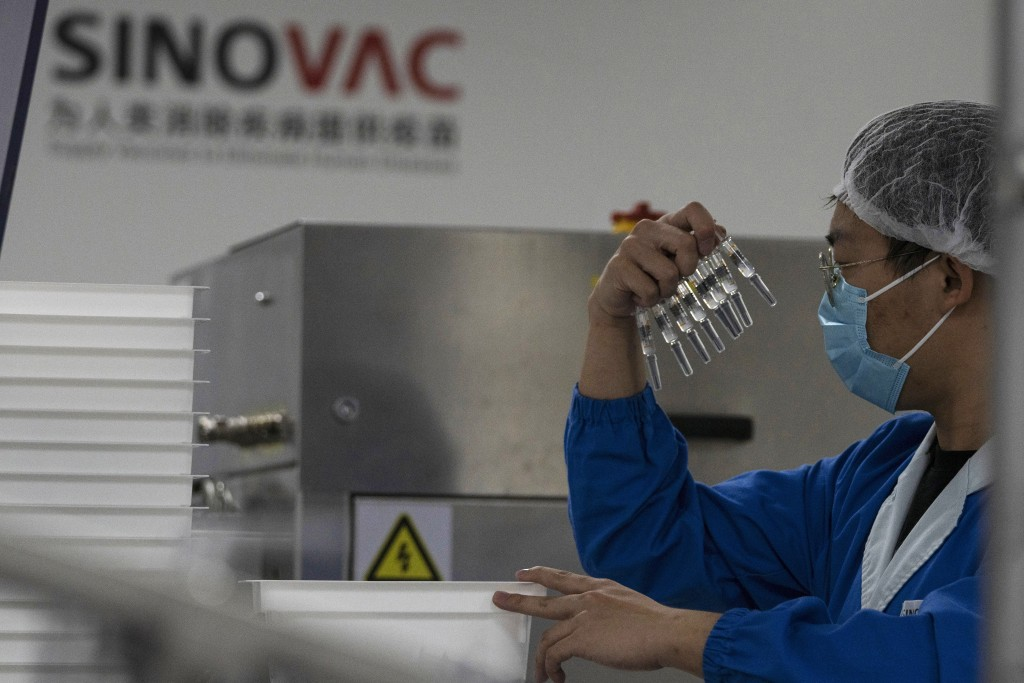 A worker inspects syringes of a vaccine for COVID-19 produced by Sinovac at its factory in Beijing on Thursday, Sept. 24, 2020. With rich countries sn...