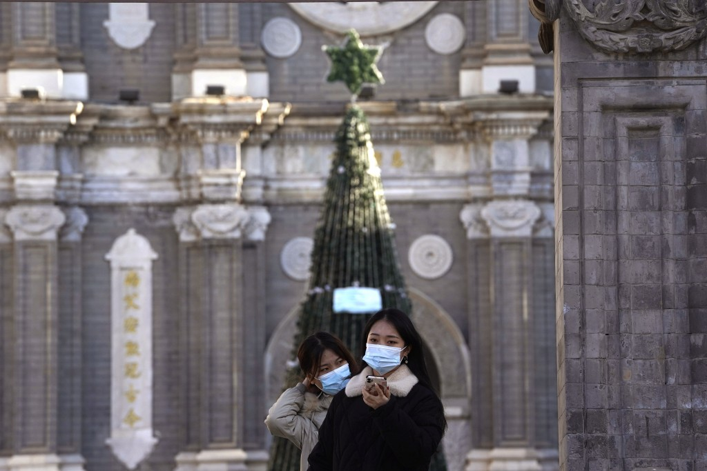 Visitors pose for a selfie outside the Wangfujing Church in Beijing on Friday, Dec. 25, 2020. Official churches in the Chinese capital abruptly cancel...