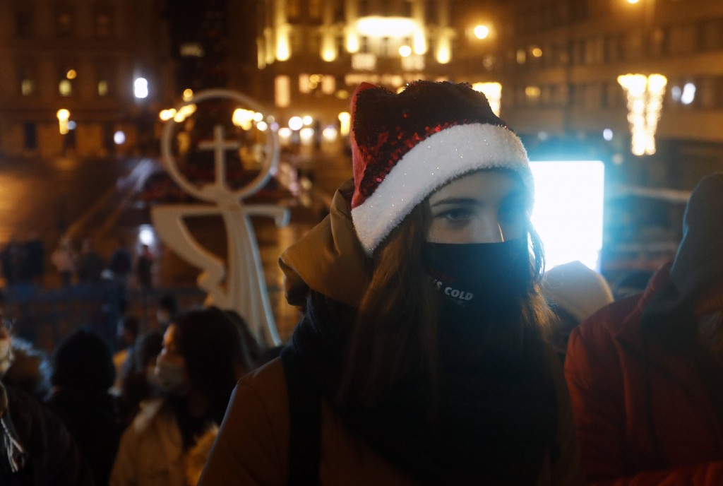 People wearing masks for protection against COVID-19 wait prior to the Christmas Eve Mass in front of St. Stephen Basilica in Budapest, Hungary, Thurs...