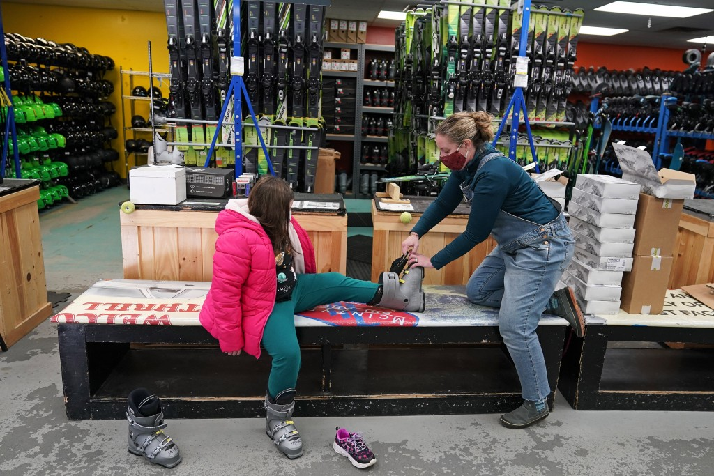 Meredith Hopkins, right, helps fit ski boots on Makenna Houghton at the ski shop at McIntyre Ski Area, Wednesday, Dec. 16, 2020, in Manchester, N.H. O...