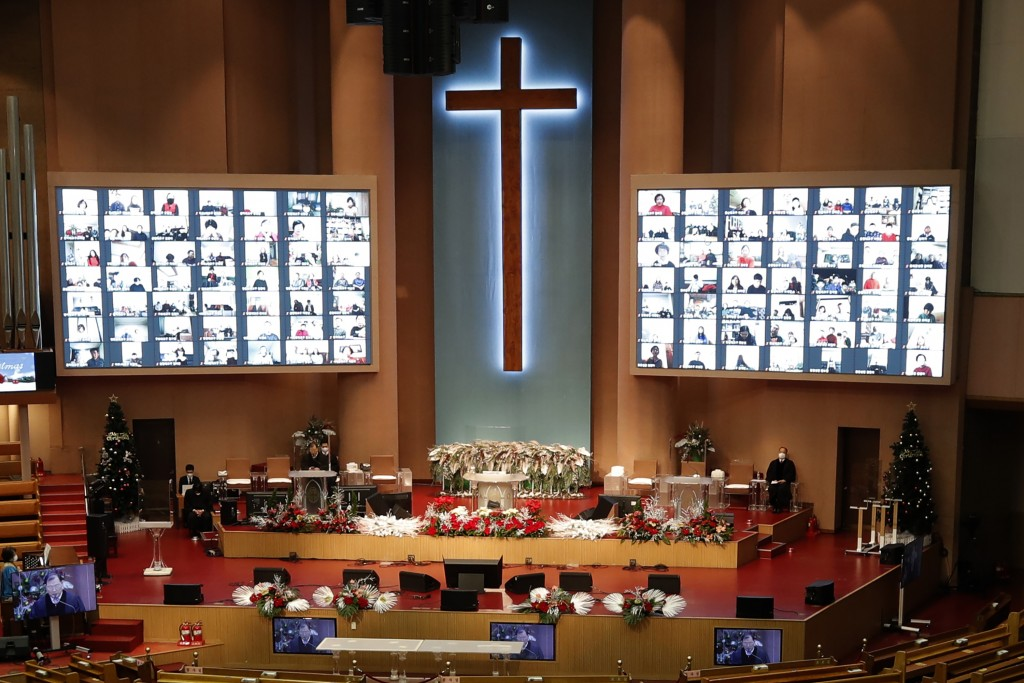 Christians on the screen attend an online Christmas service for social distancing and a precaution against the coronavirus at the Yoido Full Gospel Ch...