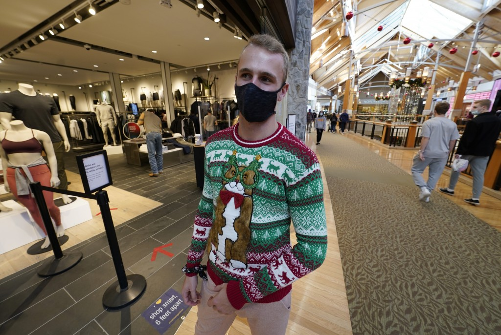 Sales associate Ethan Loper wears a festive sweater while greeting last-minute shoppers at the entry to the Lululemon store in Park Meadows Mall late ...