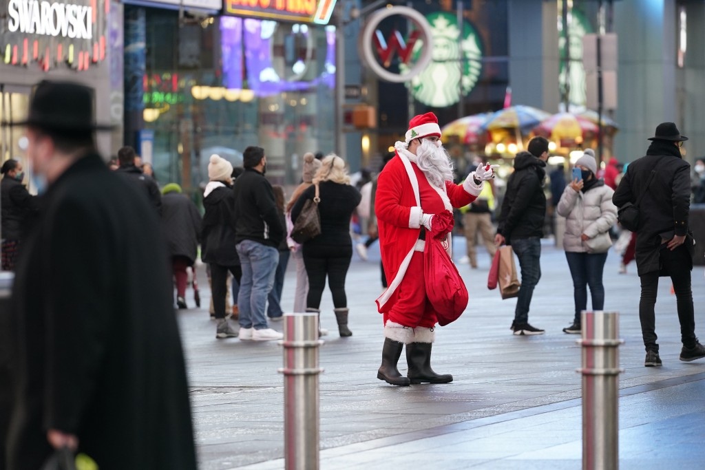 A man dresssed as Santa Claus waves at passersby, Thursday, Dec. 24, 2020, on Christmas Eve in Times Square in New York. (AP Photo/Kathy Willens)