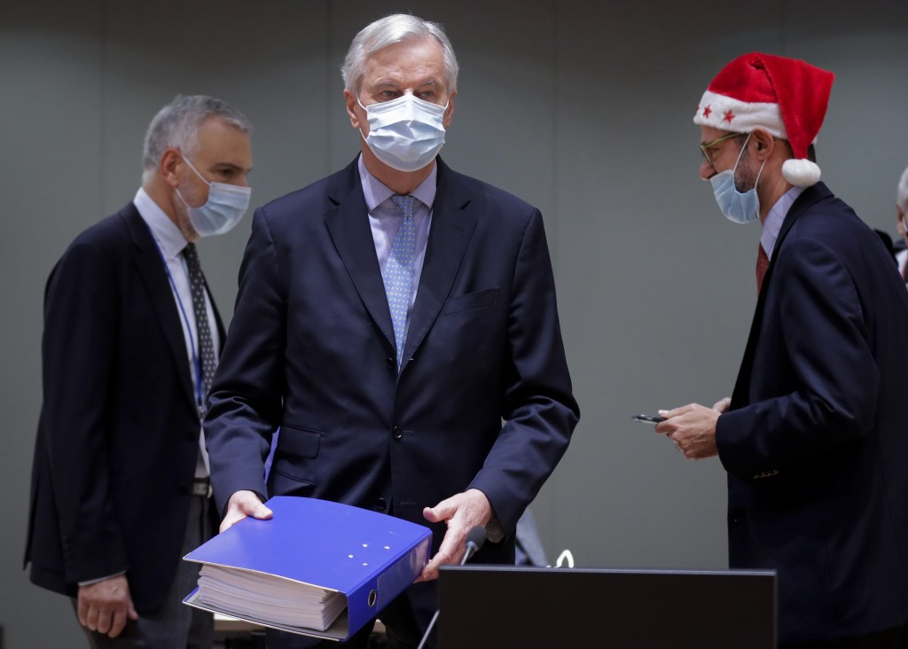 A colleague wears a Christmas hat as European Union chief negotiator Michel Barnier, center, carries a binder of the Brexit trade deal during a specia...