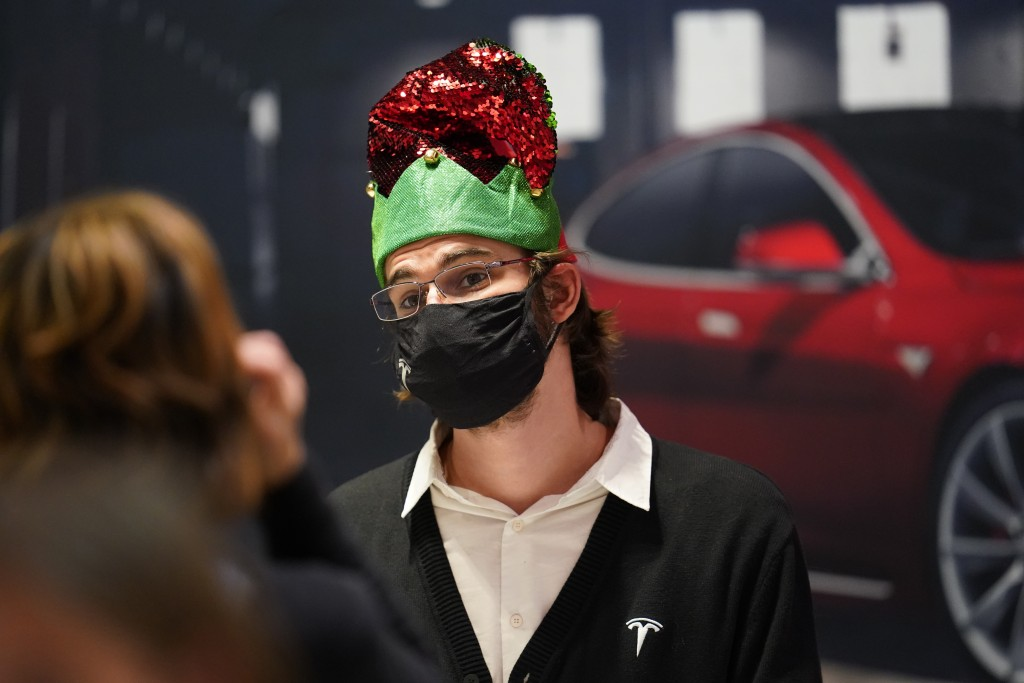 A sales associate at the Tesla store wears holiday garb while talking with a prospective buyer as last-minute shoppers search for Christmas Eve deals ...