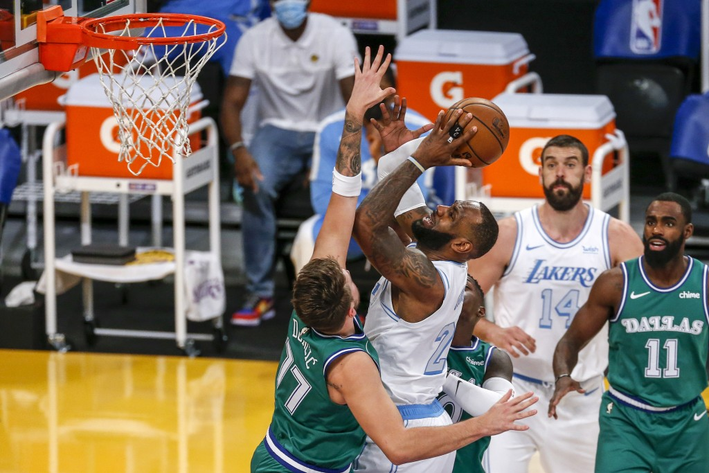 Los Angeles Lakers' LeBron James (23) goes to the basket while defended by Dallas Mavericks' Luka Doncic (77) during the first half of an NBA basketba...