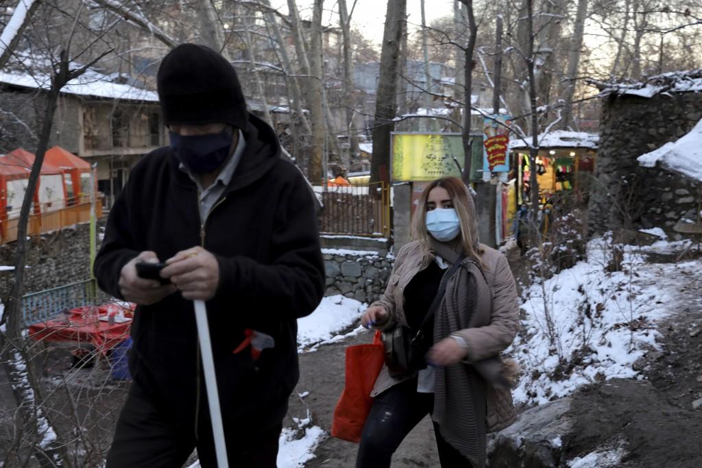 People wearing protective masks hike at the Darakeh mountainous area, north of the capital Tehran, Iran, Friday, Dec 25, 2020. (AP Photo/Ebrahim Noroo...