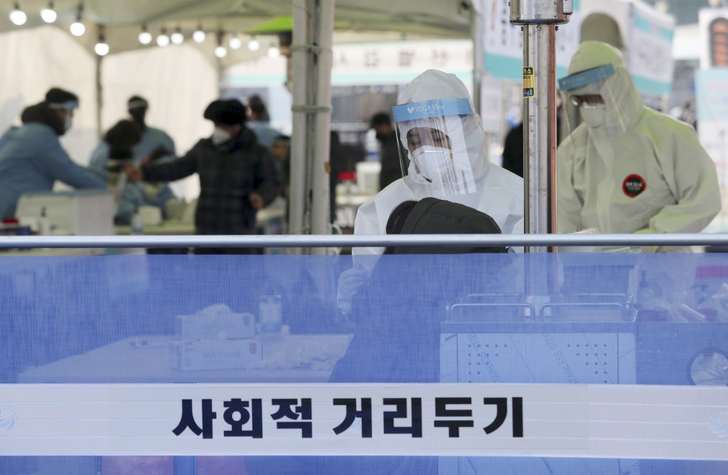 A medical worker wearing protective gear takes sample during a COVID-19 testing at coronavirus testing site in Seoul, South Korea, Saturday, Dec. 26, ...