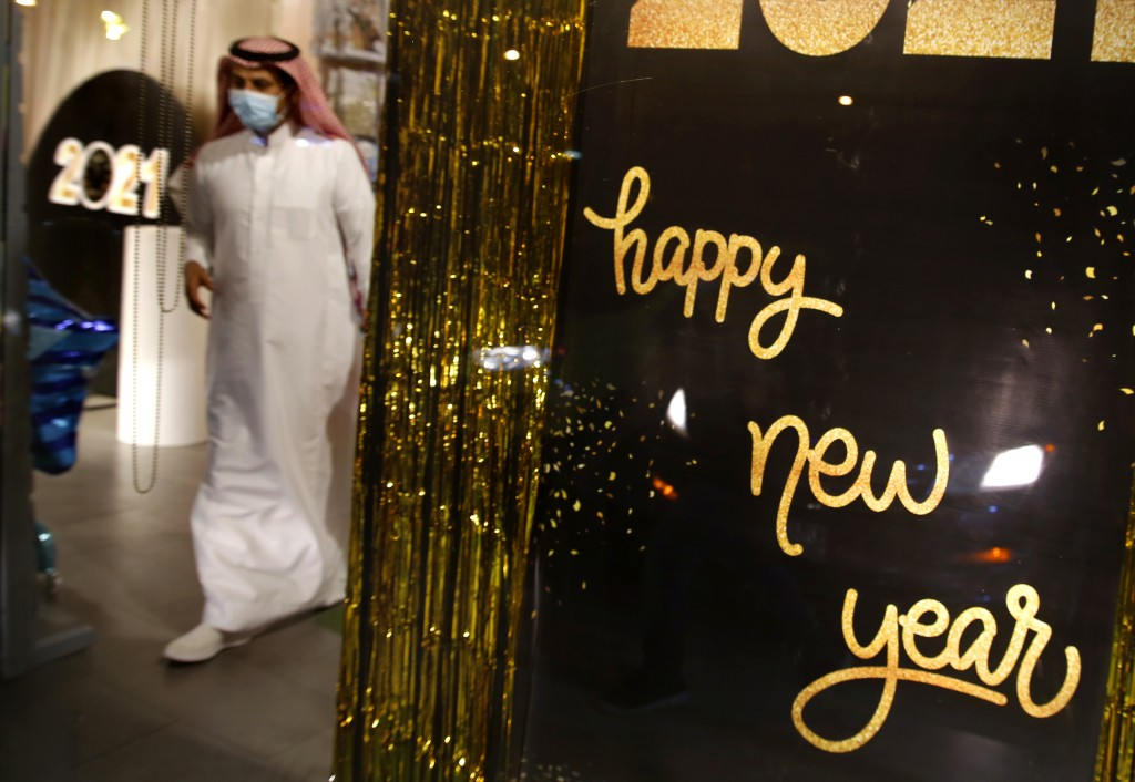 A man wearing a mask to protect from the coronavirus leaves a gift shop decorated for the New Year in Jiddah, Saudi Arabia, Friday, Dec. 25, 2020. (AP...
