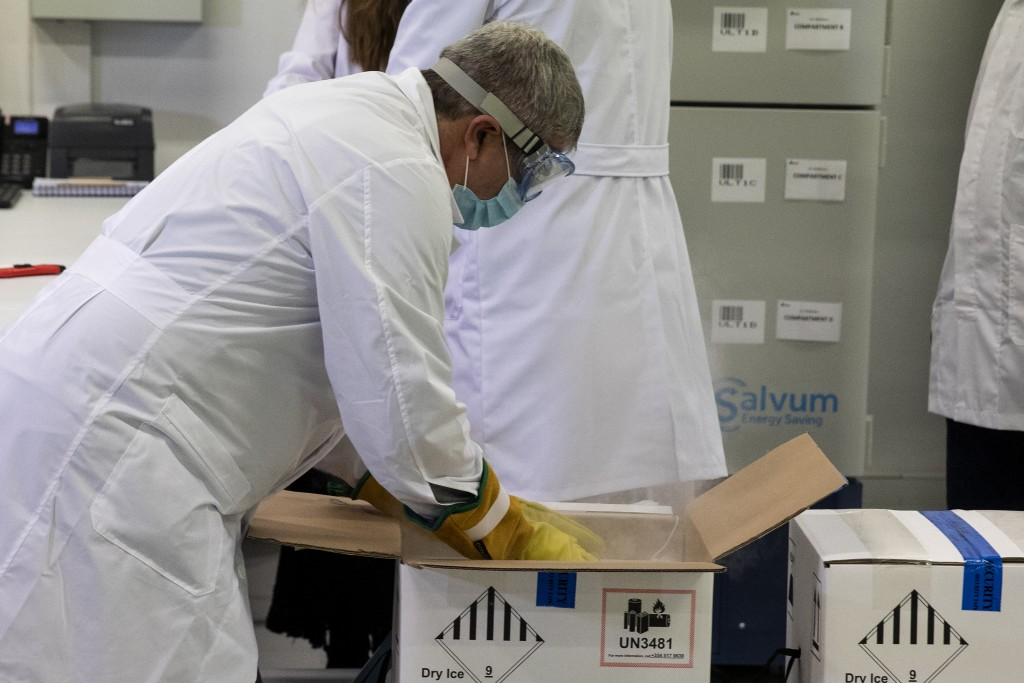 Employees of a Greek healthcare logistics company unbox packages containing vaccines against COVID-19, at Kryoneri village, near Athens, Greece, Satur...