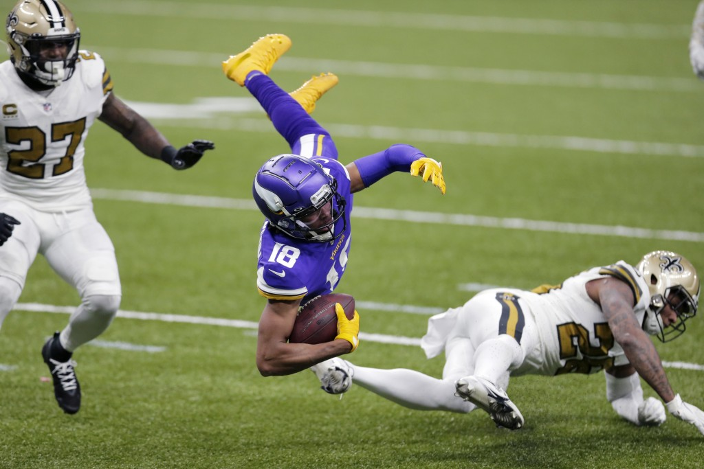 Minnesota Vikings wide receiver Justin Jefferson (18) is tripped up by New Orleans Saints cornerback Ken Crawley as strong safety Malcolm Jenkins (27)...