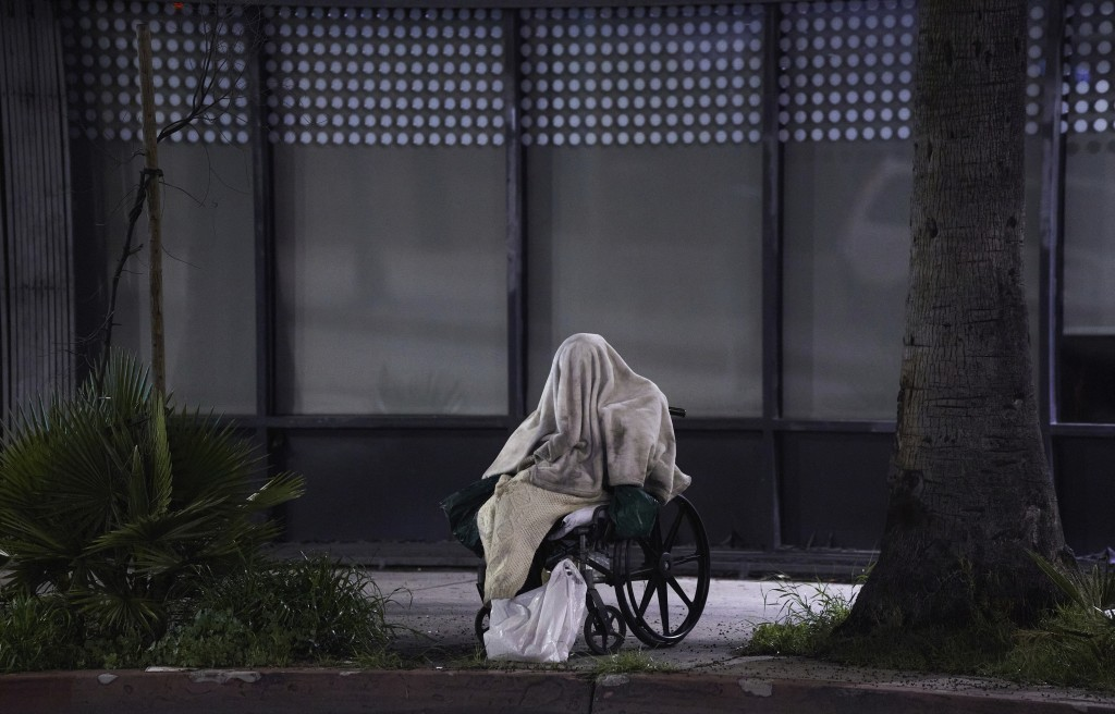 FILE - In this April 6, 2020, file photo, a homeless person sits in a wheelchair during rainy weather on Sunset Boulevard in the Echo Park neighborhoo...