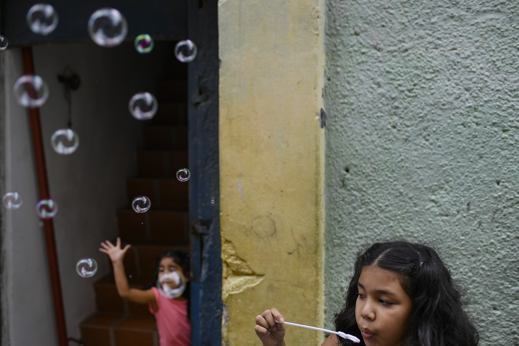 A girl plays with soap bubbles with her sister at the Catia neighborhood on Christmas Day in Caracas, Venezuela, Friday, Dec. 25, 2020, amid the new c...