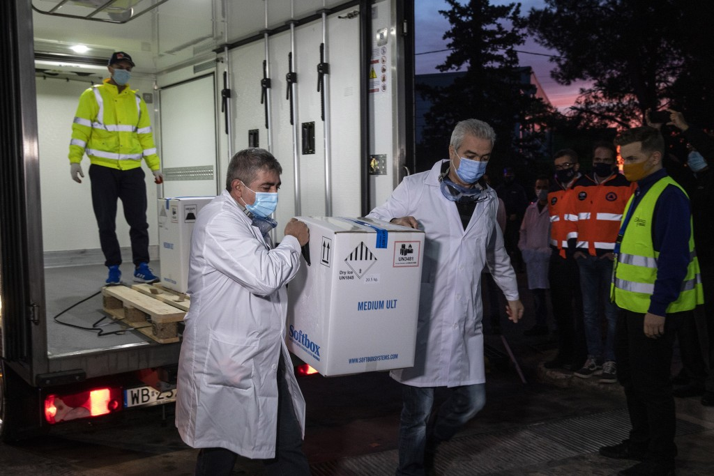 Two employees of a Greek healthcare logistics company unload a box containing vaccines against COVID-19, at Kryoneri village, near Athens, Greece, Sat...