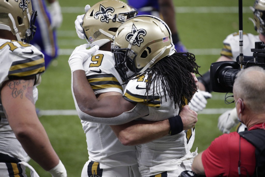 New Orleans Saints running back Alvin Kamara (41) hugs quarterback Drew Brees (9) after scoring his sixth touchdown of the game, tying the NFL record ...