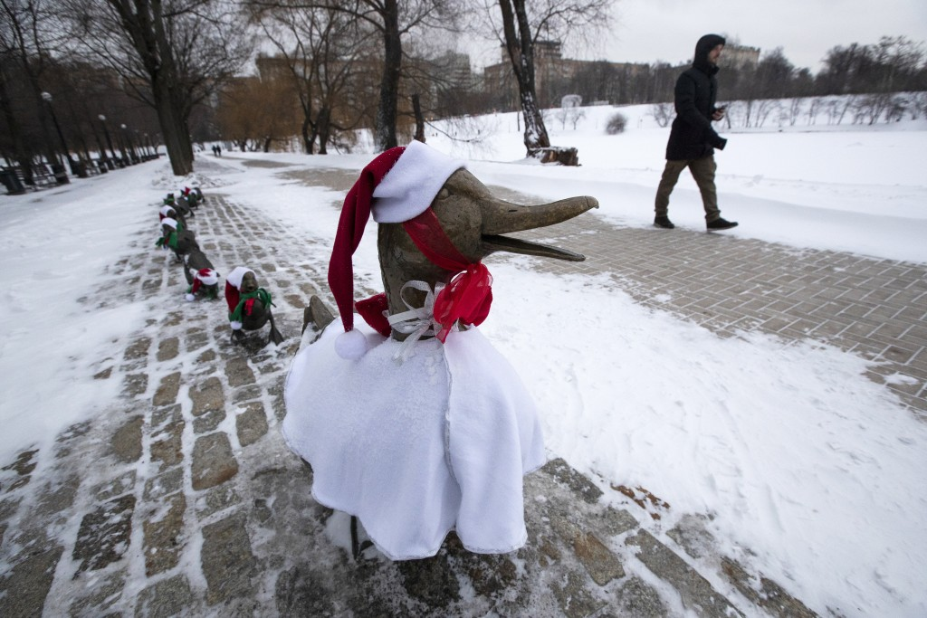 """A man passes a sculpture """"Make Way for Ducklings"""" dressed in Christmas costumes in Moscow's Novodevichy Park, Russia, Friday, Dec. 25, 2020. The copy ..."""